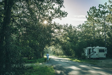 Man Walking A Dog Past An RV At A Central Florida Camp Ground On An Early Summer Morning