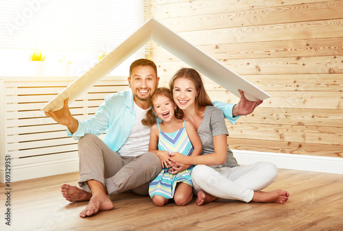 Fototapeta concept housing   young family. Mother father and child in new house with  roof obraz