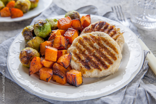 Photo Stands Brussels Diet food. Grilled chicken cutlets, roasted sweet potato and brussel sprout