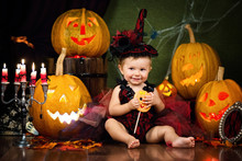 Little Witch Laughs With Candy In The Hands Among The Pumpkins And Candles.