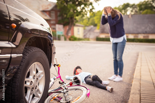 Fotografía  Accident. Girl on the bicycle crosses the road in front of a car