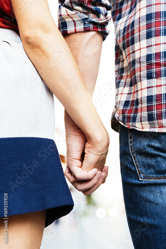 Close up of love couple holding hands.