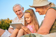Child holding tablet, grandparents. Smiling people looking at gadget.