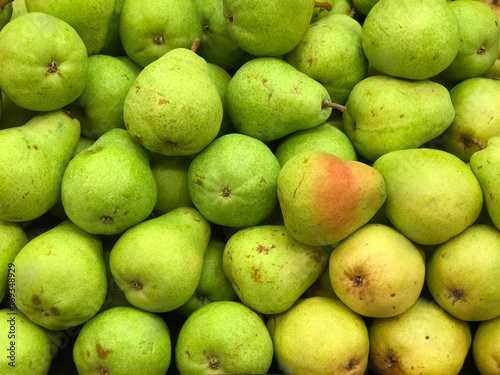 Photo Green and Yellow Pears on Display in a Market Produce Bin