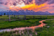 canvas print picture - Golden Fiery Sunset at Grand Teton - A colorful spring sunset at Teton Range, seen from an abandoned old ranch in Mormon Row historic district, in Grand Teton National Park, Wyoming, USA.