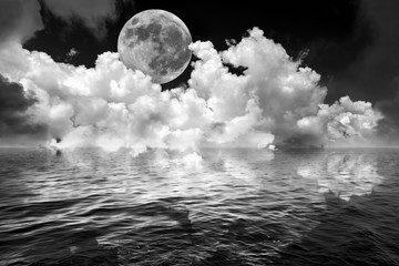 Fototapeta Czarno-biały Full moon and clouds in dark fantasy night sky reflected in wavy ocean water