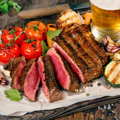 Fototapeta Do steakhouse Sliced rare grilled steak with grilled vegetables and lager beer