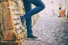 A Girl Wearing Jeans And Sneakers Leans On A Brick Wall In The Historic Part Of Town