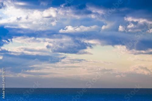 Plakat Spokojny morze z chmurnym niebem w tle - pojęcie wizerunek z kopii przestrzenią