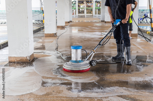 Fotografie, Obraz  Worker cleaning sand wash exterior walkway using polishing machine and chemical