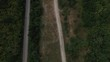 Aerial view flying over old patched two lane forest road