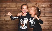 Holiday Halloween. Funny Funny Sisters Twins Children In Carnival Costumes Skeleton  On Wooden  .