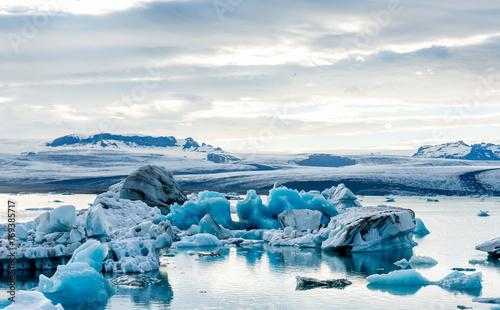 Plakat Lodowata laguna w Iceland, chmurna pogoda, góry na horyzoncie. Jezioro polodowcowe odbija niebo