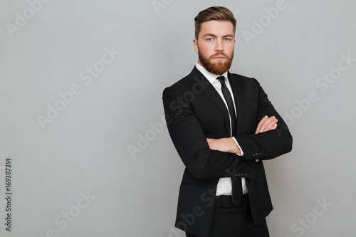 Fotomural Confident young businessman in suit standing with arms folded