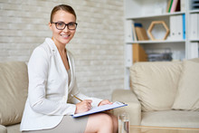 Portrait Of Beautiful Female Psychologist Wearing Glasses Posing With Clipboard In Therapy Office Smiling To Camera