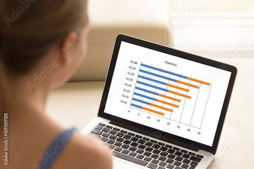 woman working with laptop analyzing financial timeline statistics