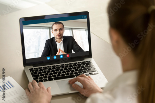 Fototapeta Businesswoman calling businessman online by video chat computer app, partners negotiating online on virtual meeting, employee reporting to boss running business remotely, close up rear view obraz na płótnie