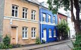 Fototapeta Londyn - Street in old town, stone wall, blue and beige color buildings, traditional houses, Copenhagen, Denmark