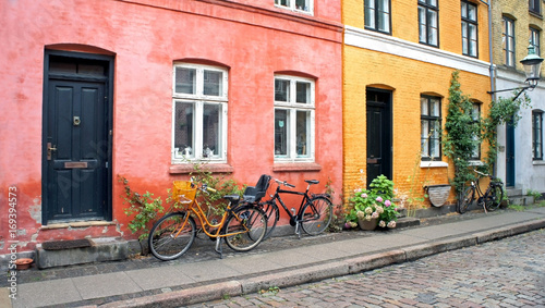 Poster Fiets Colorful street, doors, windows, red and yellow walls and bikes with basket in old town, Copenhagen, Denmark