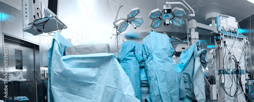 Foto Panoramic image of the modern operating room with the personnel working with the