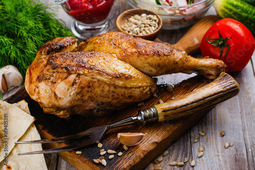 Roasted chicken with pita bread, tomato sauce and fresh raw vegetables on wooden table