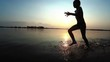 Happy Child Runs Along the Beach at Sunset. Slow Motion. Silhouette of Little Boy running on the water on the River Shore. Boy is running on the beach, raises splashes