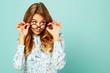 Leinwanddruck Bild Pretty thoughtful girl wearing glasses over blue background