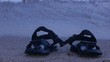 Black beach sandals on the seashore