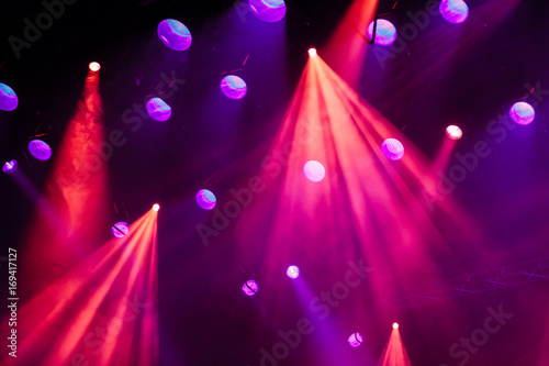 Lighting equipment on the stage of the theatre during the performance. The light rays from the spotlight through the smoke. Red and purple beams.