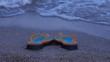 Multicolored beach sandals on the seashore