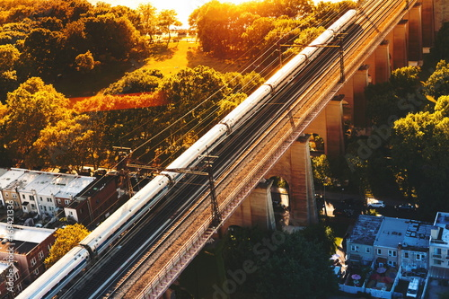 Poster  Aerial view of the of a train crossing the Hell Gate Bridge over the East River