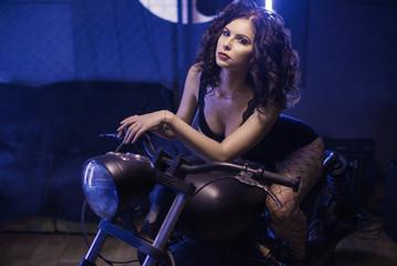 Fototapeta na wymiar Young sexy woman sitting on motorcycle.