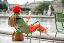 Young Stylish Woman In Red Cap And Pants Sitting With Glass Of Wine On The Famous Green Chairs In Tuileries Garden In Paris