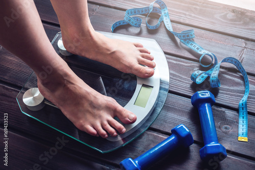 Fotomural Female feet standing on electronic scales, dumbbells and measuring tape