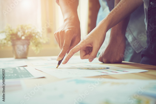 Hand pointing to a financial document on the desk. Between the agreed form of work to send customers. Teamwork ideas work best.