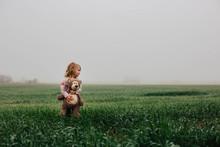 Girl With Teddy Bear In Field