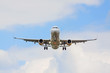 airplane flying overhead - landing / takeoff - blue sky with clouds