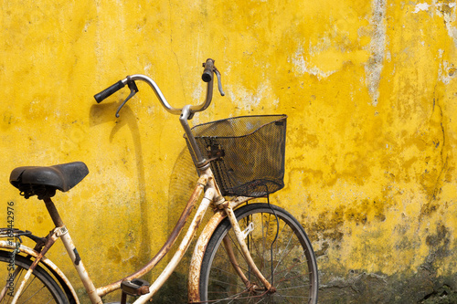 Fotobehang Fiets Old bicycle against old yellow wall on a street of Hanoi old town, Vietnam.