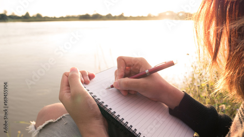 Fotografía  Close up hand of young woman with pen writing on notebook at riverside in the evening