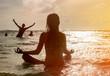 Silhouette of woman making meditation near the ocean
