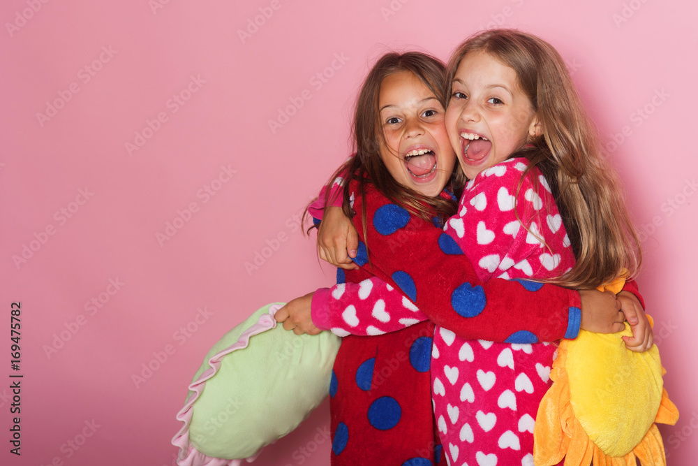Fototapety, obrazy: Girls in colorful polka dotted pajamas hold funny pillows