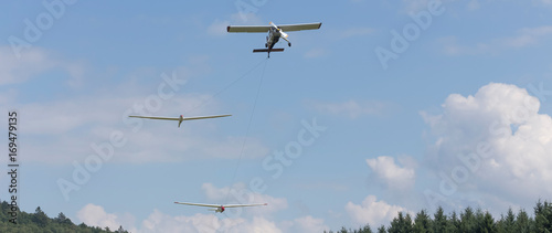 two sailplanes beeing towed from a motorplane