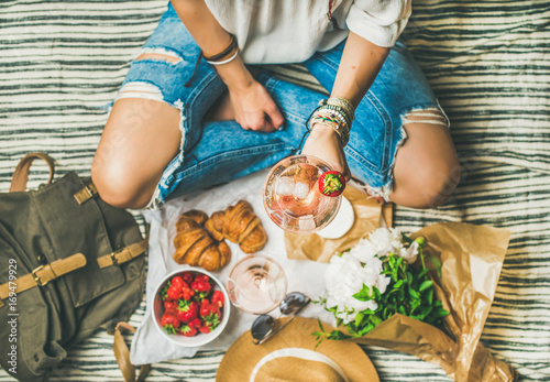 Keuken foto achterwand French style romantic picnic setting. Woman in jeans holding glass of rose wine with strawberries, croissants, brie cheese, sunglasses, peony flowers on blanket, top view. Outdoor gathering concept