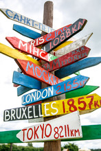 Pillar With Direction To Different Capitals Of The World Indicated In A Street Sign.