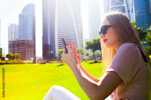Sun shines over pretty lady sitting on green lawn between skyscrapers in Dubai Canvas Print