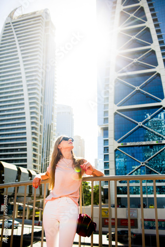 Bright sun shines between skyscrapers over lady leaning her elbows on handrails Canvas Print