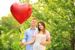 Lovely couple with heart shaped balloon in park on sunny day