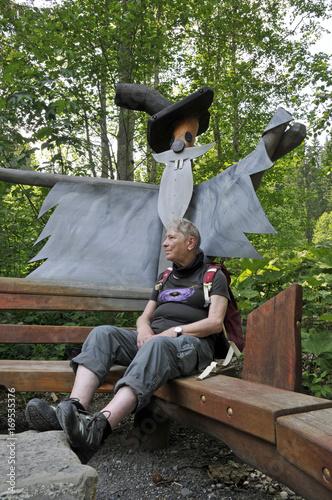Fototapeta seniorin sitzt im wald bei einer fantasiefigur obraz na płótnie