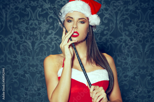Fotografie, Obraz  Sexy santa woman posing with whip on vintage background