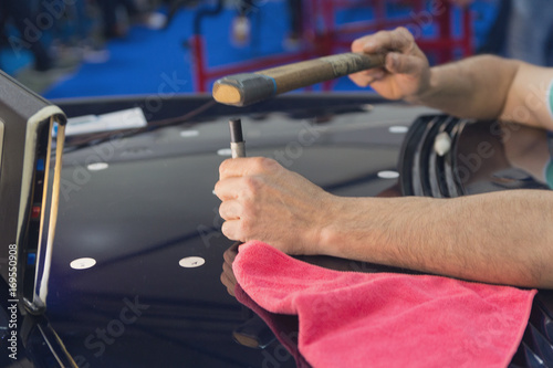 Fotografie, Obraz  Hands of the master during the work on the straightening of the car's hood